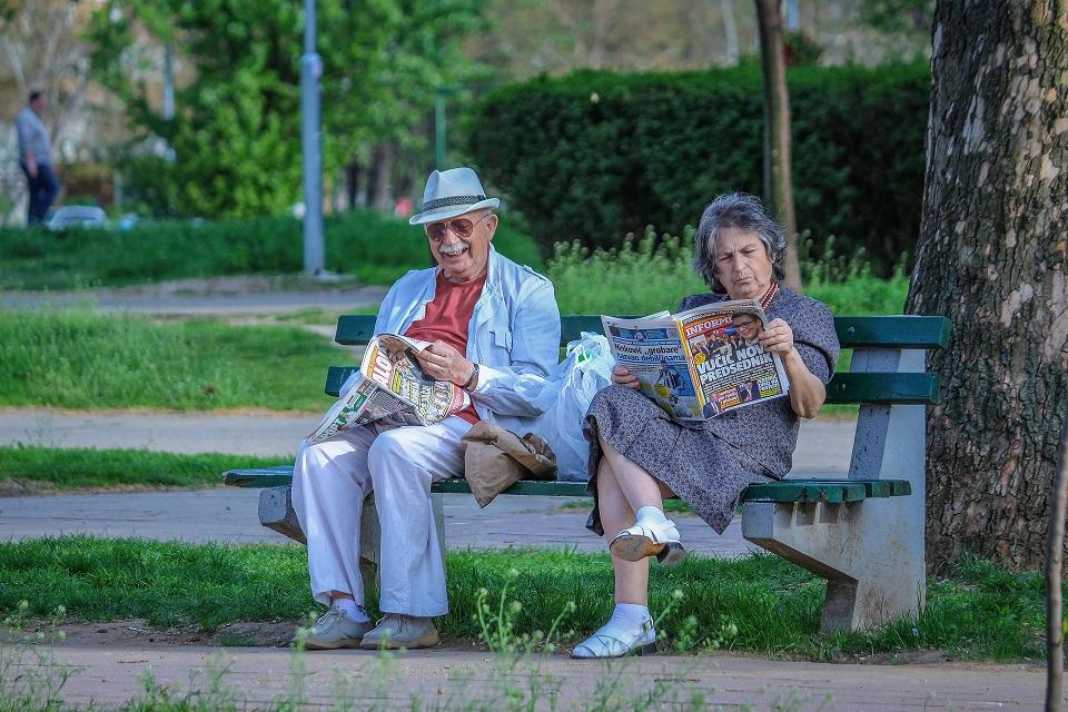 pareja de Adultos Mayores leyendo y sentados en un banco de un parque